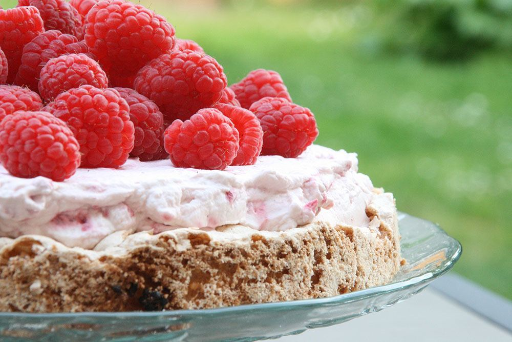 Opskrift på lækker sommerkage af mandel-hindbærbund, hindbærskum og friske hindbær